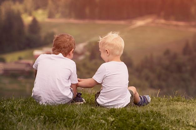 Deux garçons sont assis sur la colline et parlent avec enthousiasme