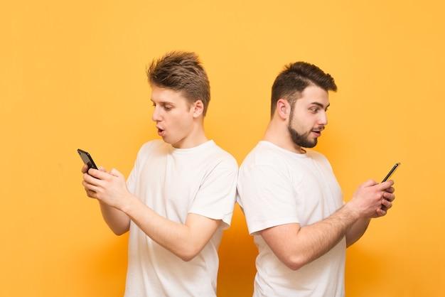 Deux garçons sont dos à dos sur le jaune, utilisent un smartphone et regardent l'écran