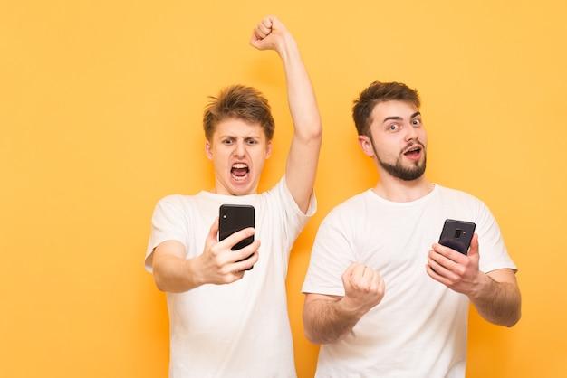 Deux garçons sont heureux sur jaune avec des smartphones dans leurs mains