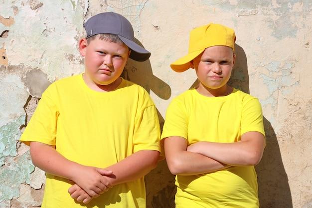 Deux garçons en t-shirts jaunes se tiennent contre un mur sous le soleil éclatant. photo de haute qualité