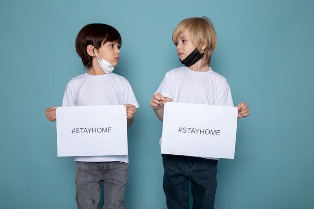 Deux garçons tenant du papier avec rester à la maison hashtag contre le coronavirus sur le bureau bleu
