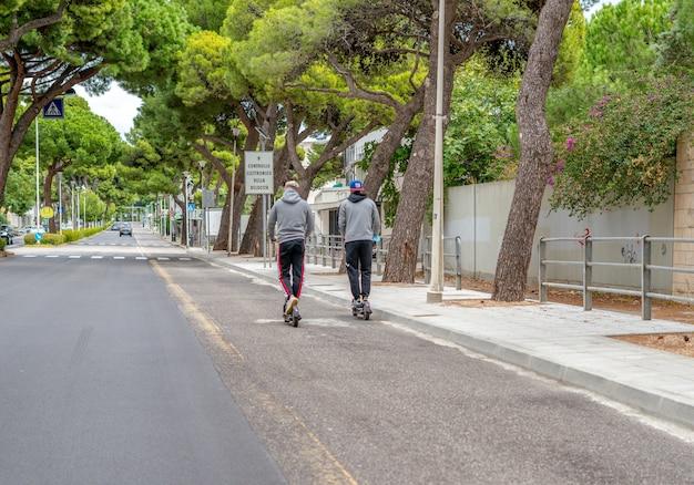 Deux garçons avec trottinette dans la ville
