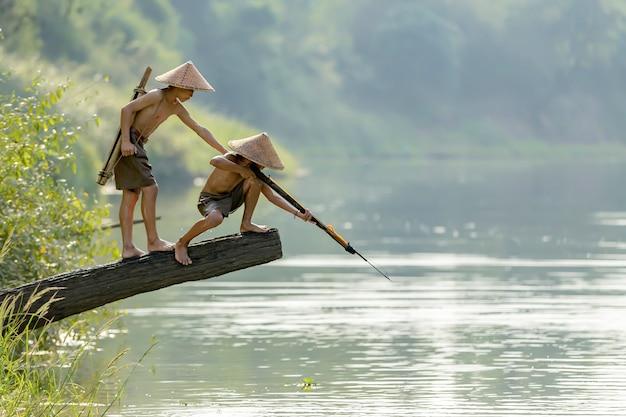 Deux garçons vont tirer sur le poisson avec un fusil pour servir de nourriture