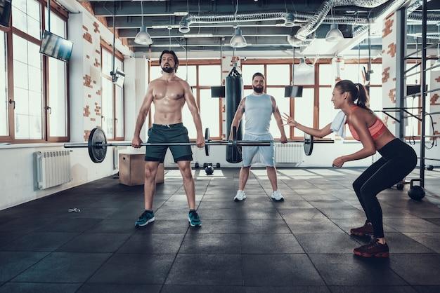 Deux gars dans la salle de gym soulevant un haltère. fille de soutien.