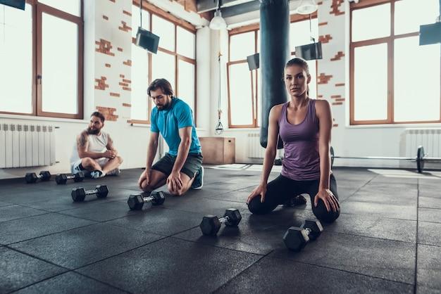Deux gars et une fille se reposent sur le sol de la salle de sport. pause.