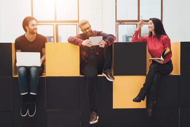 Deux gars et une fille sont assis dans des meubles modernes.