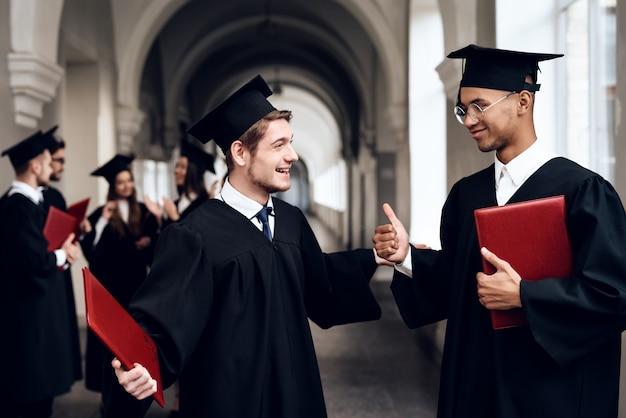 Deux gars en robe parlent à l'université.