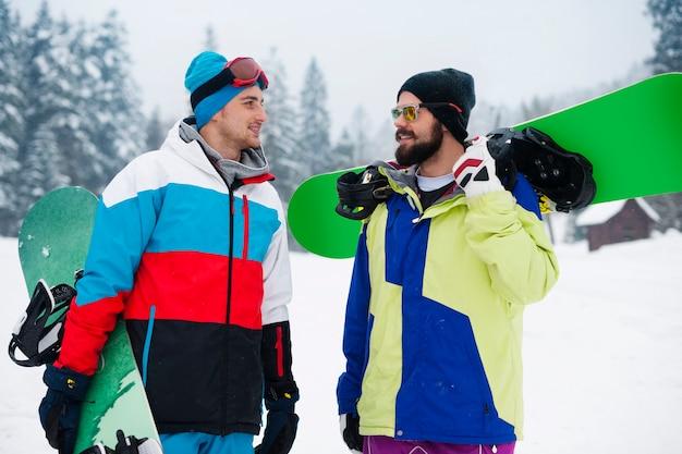Deux gars avec des snowboards pendant les vacances d'hiver