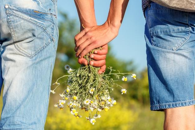 Deux gars tenant par la main avec un bouquet de concept de relation de fleurs