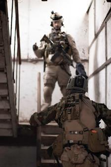 Deux gars en uniforme militaire américain se tiennent dans les escaliers jeu de sport airsoft forces militaires simu