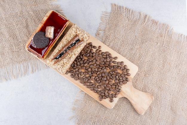 Deux gâteaux et grains de café sur planche de bois. photo de haute qualité