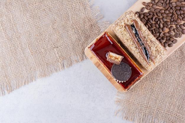 Deux gâteaux et grains de café sur planche de bois.