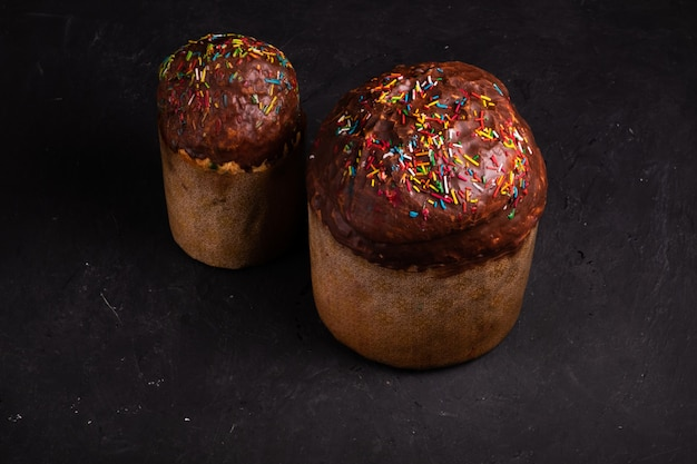 Deux gâteaux de pâques saupoudrés de chocolat et saupoudrés de bonbons se tiennent sur une surface noire