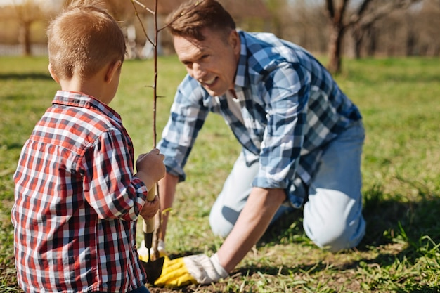 Deux générations de mâles travaillant dans un jardin familial et prenant soin d'un arbre de transplantation en recouvrant le sol avec un compost