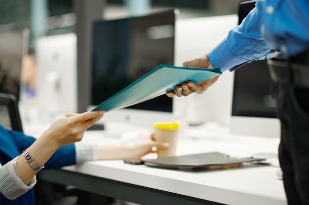 Deux gestionnaires échangent des documents dans le bureau informatique