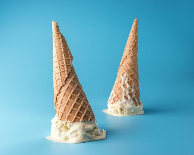 Deux glaces fondues avec des cornets de crème glacée sur fond bleu pastel