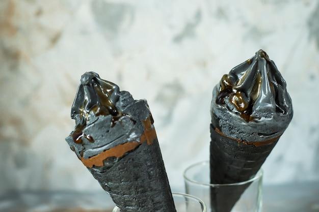 Deux glaces noires dans des cônes de gaufres sur fond gris