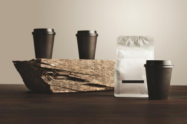 Deux gobelets en papier à emporter noir non focalisé avec bouchons fermés isolés sur la brique en bois sur la table