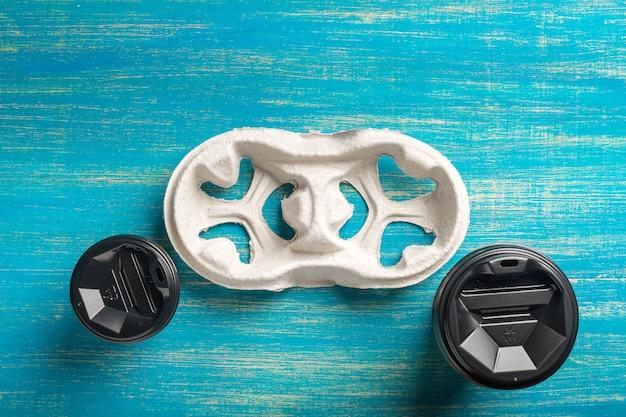 Deux gobelets en papier jetables de café et un porte-gobelet jetable sur une surface en bois bleue