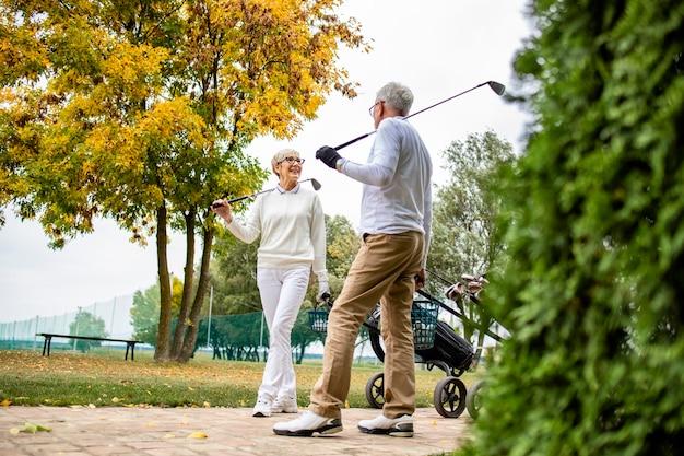 Deux golfeurs seniors élégants jouant au golf ensemble et profitant de leur temps libre à la retraite.