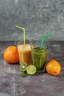 Deux grands verres de jus d'orange et un smoothie banane-orange kiwi et épinards entouré de moitiés de fruits sur un fond de béton gris. le concept de perdre du poids et une bonne nutrition.