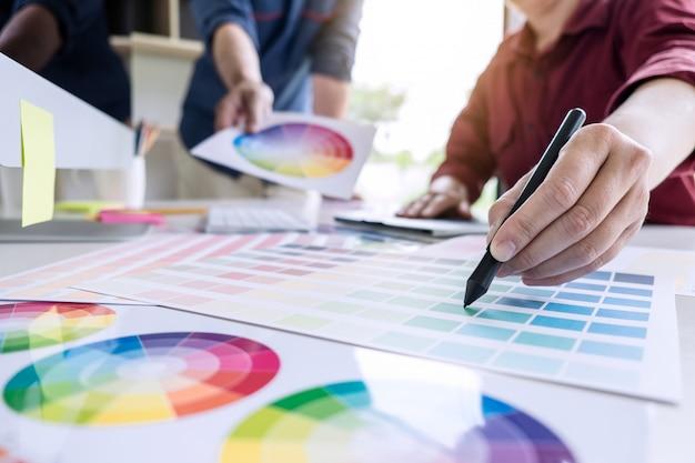 Deux graphistes créatifs travaillant avec des collègues sur la sélection des couleurs et des échantillons de couleurs