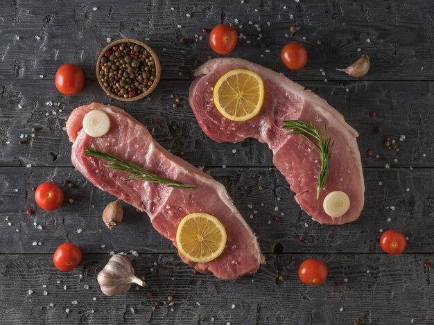 Deux gros steaks de porc au citron, tomates, épices et ail sur une table en bois. ingrédients pour la cuisson des plats de viande. la vue depuis le sommet.