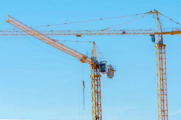 Deux grues de construction jaunes sur fond de ciel bleu