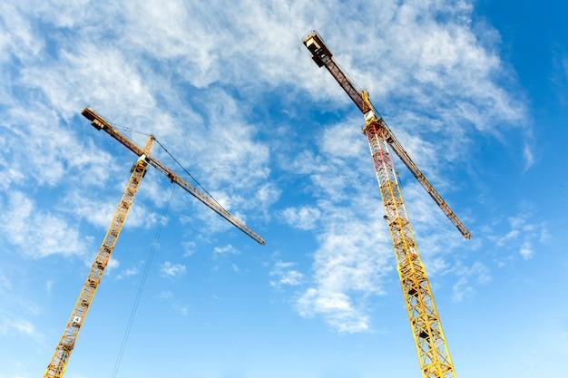 Deux grues à tour hautes travaillent à la construction de nouvelles maisons. grand angle.