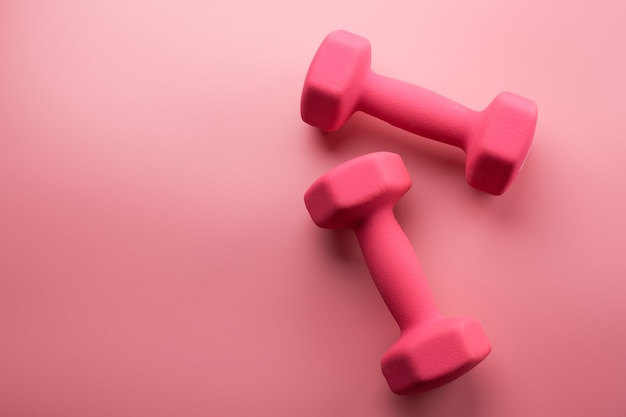 Deux haltères femelles roses isolés sur fond rose gros plan avec espace de copie. concept de remise en forme, perte de poids et activité sportive, vue de dessus, mise à plat