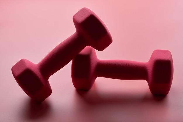 Deux haltères femelles roses isolés sur gros plan fond rose avec espace de copie. concept de remise en forme, perte de poids et activité sportive