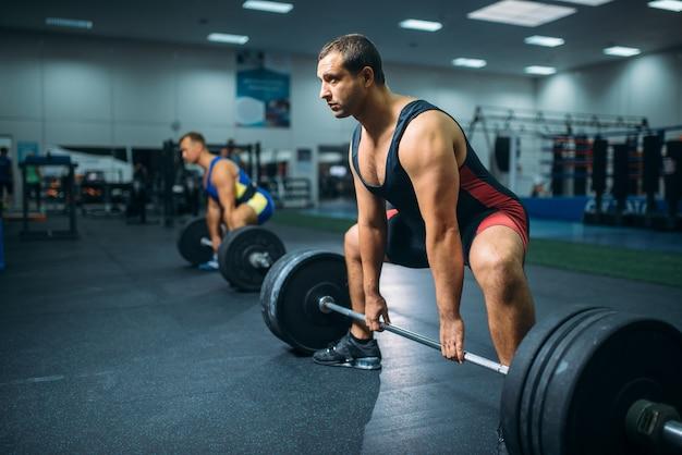 Deux haltérophiles forts faisant de l'exercice avec des haltères, intérieur de la salle de sport.