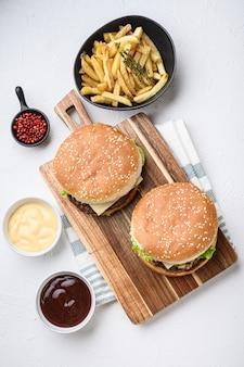 Deux hamburger de boeuf haché et frites sur une surface texturée blanche.