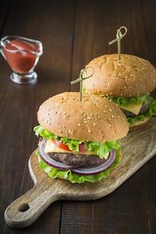 Deux hamburgers de boeuf frais avec des légumes sur une planche de bois.