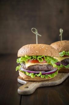 Deux hamburgers de boeuf frais avec des légumes sur une planche de bois