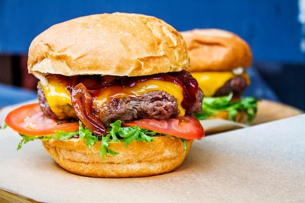 Deux hamburgers avec côtelette de boeuf et légumes en gros plan.