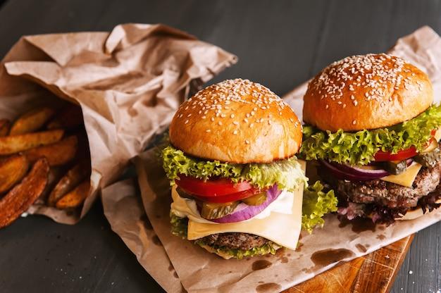 Deux hamburgers faits maison délicieux et appétissants utilisés pour hacher le bœuf. sur la table en bois.