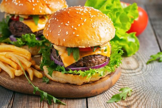Deux hamburgers faits maison avec des pommes de terre frites sur une table en bois.