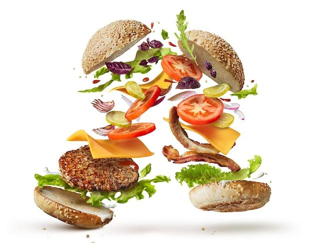 Deux hamburgers avec des ingrédients volants isolés