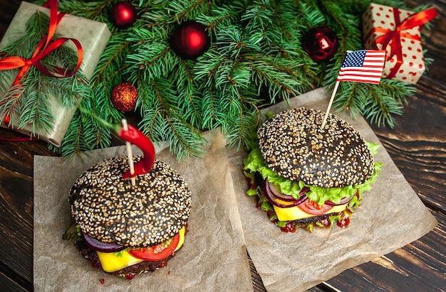 Deux hamburgers noirs de noël avec du noir américain, de la laitue, de la tomate et des frites. fond en bois