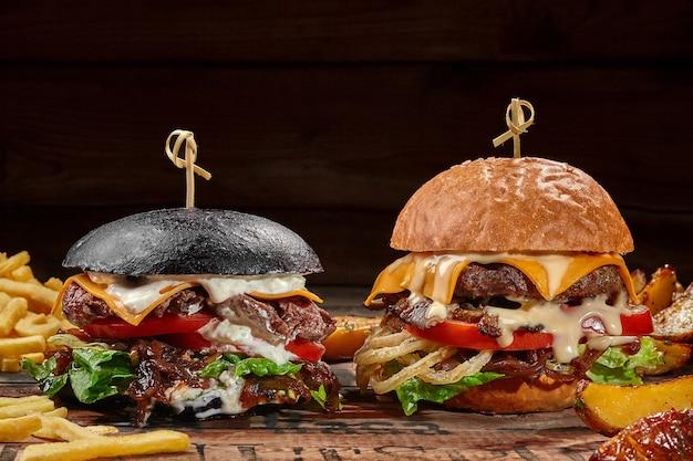Deux hamburgers en petits pains blancs et noirs avec pommes de terre frites