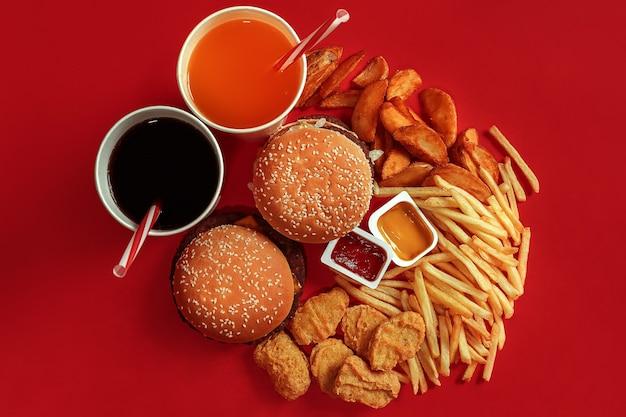 Deux hamburgers et sauces frites et boissons sur fond rouge vue de dessus de restauration rapide à plat avec...
