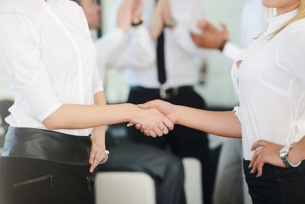 Deux handshaking de femmes d'affaires après que l'affaire femelle soit faite