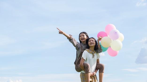 Deux heureux asain girl holding balloon