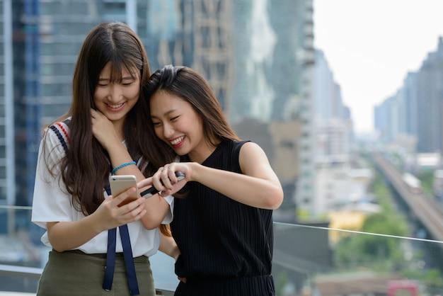 Deux heureux jeunes belles femmes adolescentes asiatiques à l'aide de téléphone ensemble contre vue sur la ville