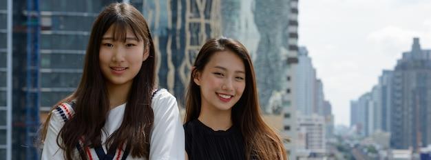 Deux heureux jeunes belles femmes adolescentes asiatiques souriant ensemble contre vue sur la ville