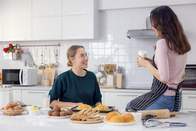 Deux heureux mignons, un beau boulanger qui prépare des bonbons les femmes se sont bien amusées dans une leçon de fabrication de pain et utilisent leurs mains pour gifler de la pâte ensemble dans la cuisine pour faire des gâteaux ensemble.