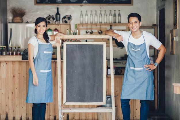 Deux heureux propriétaires de petites entreprises prêts à ouvrir leur café