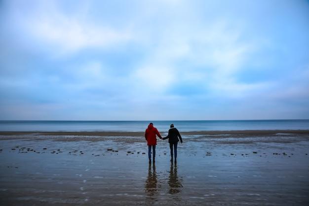 Deux hipsters debout sur la plage froide. couple élégant s'embrassant et se tenant la main. histoire d'amour près de l'océan. saison d'hiver sur la mer. homme en veste rouge.