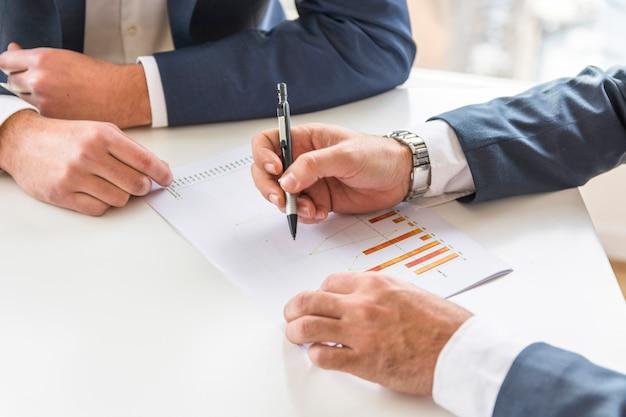 Deux homme d'affaires analysant le rapport d'activité sur le bureau blanc